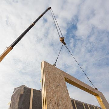 Crane lifting modular walls into place
